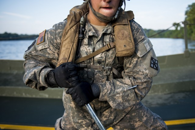 Spc. Trevor Reilly, from Palmyra, Va., an Army Reserve bridge crew member with the 310th Engineer Company (Multi-Role Bridge), cranks a hydraulic ramp to connect an improved ribbon bridge to shore during Operation River Assault 2015, a bridging training exercise involving Army Engineers and other support elements to create a modular floating bridge on the water across the Arkansas River at Fort Chaffee, Ark., Aug. 4, using improved ribbon bridge bays. The entire training exercise lasted from July 28 to Aug. 4, 2015, involving one brigade headquarters, two battalions and 17 other units, to include bridging, sapper, mobility, construction and aviation companies. (U.S. Army photo by Master Sgt. Michel Sauret)