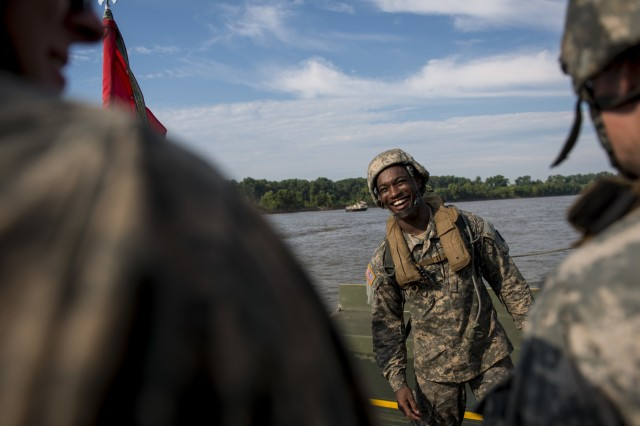 "Spc. Markquise Carey, of Salisbury, Md., laughs with fellow Army Soldiers from the 310th Engineer Company (Multi-Role Bridge), from Fort A.P., Hill, Va., after tossing their executive officer into the Arkansas River as a traditional ""baptism"" during Operation River Assault 2015, a bridging training exercise involving Army Engineers and other support elements to create a modular floating bridge at Fort Chaffee, Ark., Aug. 4, using improved ribbon bridge bays. The entire training exercise lasted from July 28 to Aug. 4, 2015, involving one brigade headquarters, two battalions and 17 other units, to include bridging, sapper, mobility, construction and aviation companies. (U.S. Army photo by Master Sgt. Michel Sauret)"