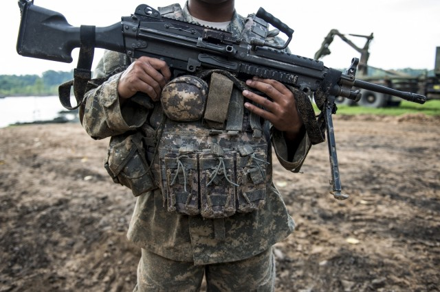 An Army Reserve Soldier from the 364th Engineer Company (Sapper), from Dodge City, Kan., holds an M249 squad automatic weapon, and is covered in sand after having helocasted in the Arkansas River for Operation River Assault 2015, a bridging training exercise involving Army Engineers and other support elements to create a modular floating bridge at Fort Chaffee, Ark., Aug. 4, using improved ribbon bridge bays. The entire training exercise lasted from July 28 to Aug. 4, 2015, involving one brigade headquarters, two battalions and 17 other units, to include bridging, sapper, mobility, construction and aviation companies. (U.S. Army photo by Master Sgt. Michel Sauret)
