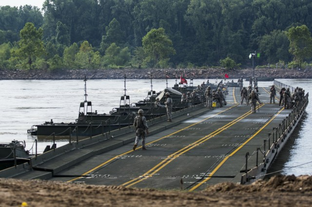 Army Reserve Soldiers work to connect two large sections of a modular floating bridge during Operation River Assault 2015, a bridging training exercise involving Army Engineers and other support elements to create a modular floating bridge on the water across the Arkansas River at Fort Chaffee, Ark., Aug. 4, using improved ribbon bridge bays. The entire training exercise lasted from July 28 to Aug. 4, 2015, involving one brigade headquarters, two battalions and 17 other units, to include bridging, sapper, mobility, construction and aviation companies. (U.S. Army photo by Master Sgt. Michel Sauret)