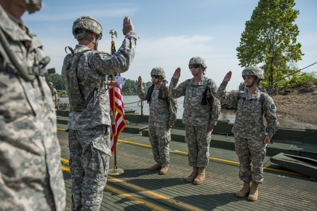 Col. Ralph Henning, of Denver, Colo., commander of the 411th Engineer Brigade, administers the oath of enlistment with three Army Reserve Soldiers from various companies to extend their military service after a modular floating bridge is assembled to cross Arkansas River during Operation River Assault 2015, a bridging training exercise involving Army Engineers and other support elements at Fort Chaffee, Ark., Aug. 4, using improved ribbon bridge bays. The entire training exercise lasted from July 28 to Aug. 4, 2015, involving one brigade headquarters, two battalions and 17 other units, to include bridging, sapper, mobility, construction and aviation companies. (U.S. Army photo by Master Sgt. Michel Sauret)
