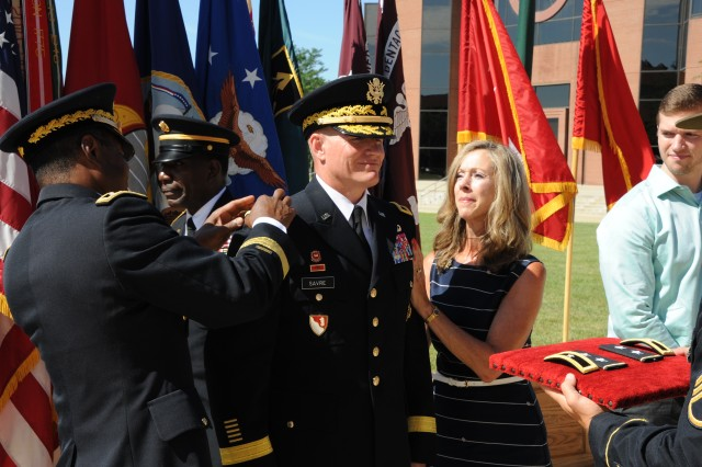 Maj. Gen. Kent Savre, Maneuver Support Center of Excellence and Fort Leonard Wood commanding general, has his two-star insignia pinned on by Lt. Gen. Thomas Bostick, U.S. Army Chief of Engineers and commanding general of the U.S. Army Corps of Engineers, and Savre's wife, Mary Beth. The promotion ceremony took place July 30 on the MSCoE Plaza.
