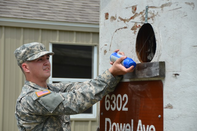 Pfc. George Funk, General Leonard Wood Army Community Hospital preventive medicine specialist, disposes of a wasp nest, after determining the nest was located where the insects could potentially harm Soldiers.