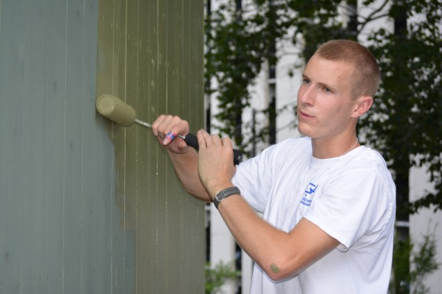 Matthew Evans, son of Master Sgt. Robert Evans, 102d Training Division, paints the fence around a garbage bin on the grounds of the Bethesda Md., Fisher House, which provides free temporary lodging to military veterans and family members while their loved ones receive care at nearby Walter Reed National Military Medical Center. Evans and nine other members of the 80th Training Command (TASS) Teen Council participated in a joint meeting with members of the 412th Theater Engineer Command and the 75th Training Command teen councils in Alexandria, Va., July 27-31, 2015. The council members helped beautify the Fisher House grounds as part of their community service requirement.