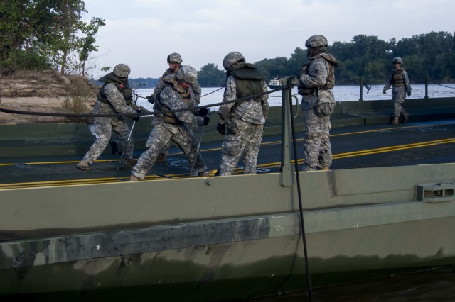 Bridge crew members with the 502nd Engineer Company (Multi-Rolled Bridge Company), from Fort Knox, Ky., assembles a pair of interior bridge bays on the Arkansas River during gap training at Fort Chaffee, Ark., Aug. 4, 2015. The entire training exercise lasted from July 28 to Aug. 7, involving one brigade headquarters, two battalions and 17 other units, to include bridging, sapper, mobility, construction and aviation companies.