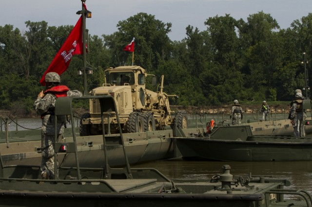 Bridge crew members with the 502nd Engineer Company (Multi-Rolled Bridge Company), and the 712th Engineer Company (Horizontal), from Fort Knox, Ky., drive a ground grader over the completed bridge on the Arkansas River during gap training at Fort Chaffee, Ark., Aug. 4, 2015. The entire training exercise lasted from July 28 to Aug. 7, involving one brigade headquarters, two battalions and 17 other units, to include bridging, sapper, mobility, construction and aviation companies.
