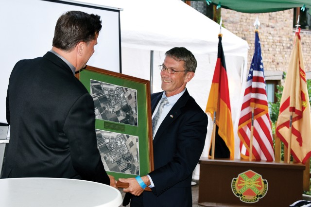 Director of Public Works Michael Sly presents Transformation Stationing Management Office Director Roger Gerber with a before-and-after photo of U.S. Army Garrison Wiesbaden at the TSMO going away event July 30.