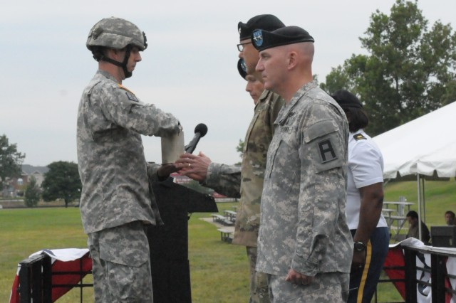 First Army Division East's Maj. Jason Rathbun (left) presents a ceremonial artillery shell to Division East's outgoing commanding general, Maj. Gen. Jeffrey L. Bailey, during the First Army Division East change of command ceremony, Fort George G. Meade, Md., Aug. 7