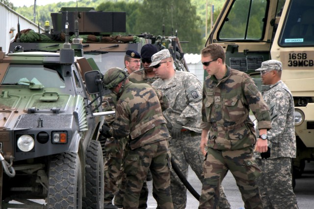 Petroleum supply specialists from the 16th Sustainment Brigade's 240th Quartermaster Company, Spc. Wayne Burch (center) and Sgt. Joey Patague, work with the French Army's 126th Infantry Regiment soldiers to refuel a vehicle at the Joint Multinational Readiness Center in Hohenfels, Germany.
