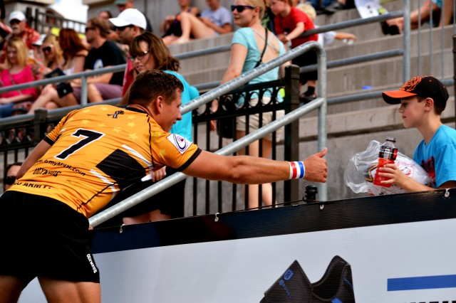 U.S. Army World Class Athlete Program rugger 1st Lt. William Holder gives his trophy rugby ball to a young spectator after helping All-Army win the 2015 Armed Forces Rugby Sevens Championship at Infinity Park in Glendale, Colo., Aug. 15, 2015.