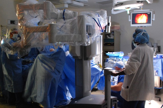 """Surgical staff """"dock"""" the da Vinci surgical system robot by a patient undergoing a laparoscopic surgical procedure at Womack Army Medical Center, Aug. 12, 2015."""