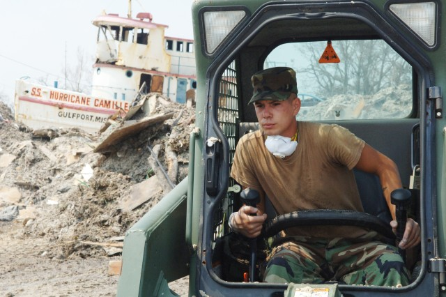 In Gulfport, Miss., Sgt. Cory B. Rees of Big Rock, Tennessee, operates a Bobcat scoop loader while wearing a surgical mask to muffle stench during clean-up operations in Gulfport. He was part of relief operations there after Hurricane Katrina, sometime in August or September of 2005.