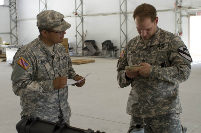 Staff Sgt. Brent Mann, right, master small unmanned aircraft system for 3rd Armored Brigade Combat Team, 1st Cavalry Division, and Sgt. Edgar Jimenez, a supply specialist with Company A, 2nd Battalion, 7th Cavalry Regiment, 3rd Armored Brigade Combat Team, check the components of the unit's new Gimbal Raven system on Fort Hood, Texas, Aug. 19, 2015.