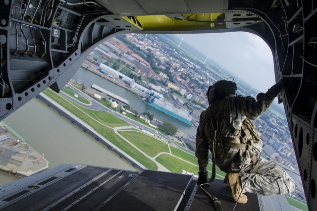 Staff Sgt. Ryan W. Azevedo,  a CH-47 Helicopter Repairer and Company Standardization Instructor for Hotel Company 1-214th Aviation Regiment, 12th Combat Aviation Brigade, observes the shipping port inside the new CH-47F MYII over Bremerhaven, Germany Aug. 21, 2015.  The new helicopters will provide 12th CAB with the latest and most cutting-edge CH-47F platform to-date that will ensure combat readiness, which incorporates reliability, maintainability improvement modifications and current modernization programs.