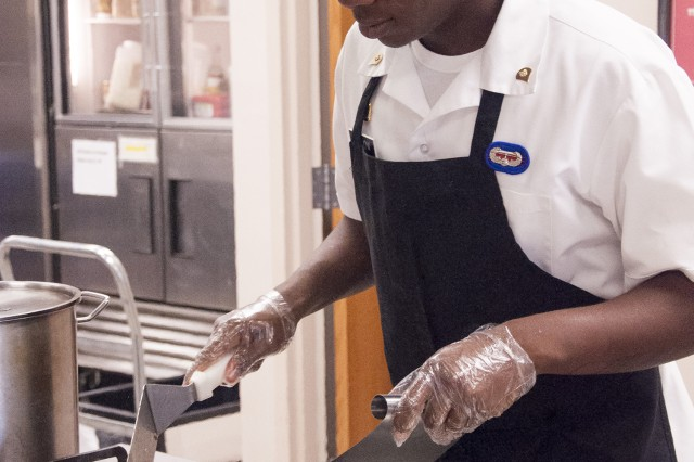 Spc. Kedrick Barlow prepares the filling for Philly cheesesteak sandwiches that were served during a luncheon, Tuesday.