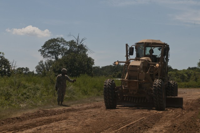 U.S. Army Reserve Sgt. Todd Hamiton directs Spc. Jordan Burke, both heavy equipment operators with the 712th Engineer Company (Horizontal) out of York, S.C., while grading a road outside Fort Chaffee, Ark., Aug. 1 during Operation River Assault 2015. The unit provided road improvements to ensure vehicles had access to the river for the culminating event, the gap crossing. (U.S. Army photo by Staff Sgt. Debralee Best)