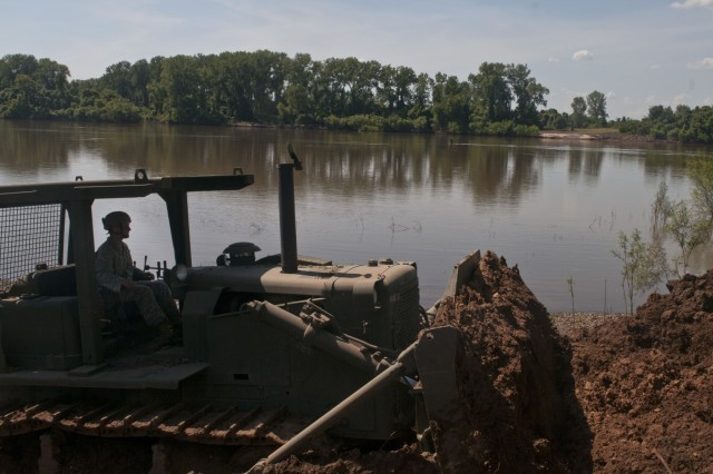 U.S. Army Reserve Sgt. Nicholas Chiodini, heavy equipment operator with the 712th Engineer Company (Horizontal) out of York, S.C., clears slip four of sediment at Fort Chaffee, Ark., Aug. 1 during Operation River Assault 2015. The unit cleared the slips of 2 to 4 inches of mud and debris to ensure vehicles had access to the river for the culminating event, the gap crossing. (U.S. Army photo by Staff Sgt. Debralee Best)
