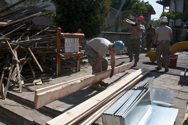 U.S. Army Reserve Spc. Christian Watts (front) stacks lumber while Spc. Jacob Nance brings another load. These construction engineer Soldiers with the 390th Engineer Company out of Chattanooga, Tenn., partnered with the Bulgarian Army to renovate a roof on Prolet Kindergarten in Veliko Tarnovo, Bulgaria, Aug. 3 to 19 for a Humanitarian Civil Assistance project funded by U.S. European Command through the U.S. Office of Defense Cooperation Bulgaria. (U.S. Army photo by Staff Sgt. Debralee Best)