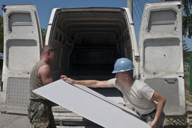 U.S. Army Reserve Pfc. Jared Poulson (right), construction engineer, 390th Engineer Company, loads drywall with Bulgarian Army Pvt. Borislav Borislavovileva. The 390th Engineer Company out of Chattanooga, Tenn., partnered with the Bulgarian Army to renovate two classrooms and a bathroom for the Tsersova Koria, Bulgaria kindergarten Aug. 3 to 19 for a Humanitarian Civil Assistance project funded by U.S. European Command through the U.S. Office of Defense Cooperation Bulgaria. (U.S. Army photo by Staff Sgt. Debralee Best)