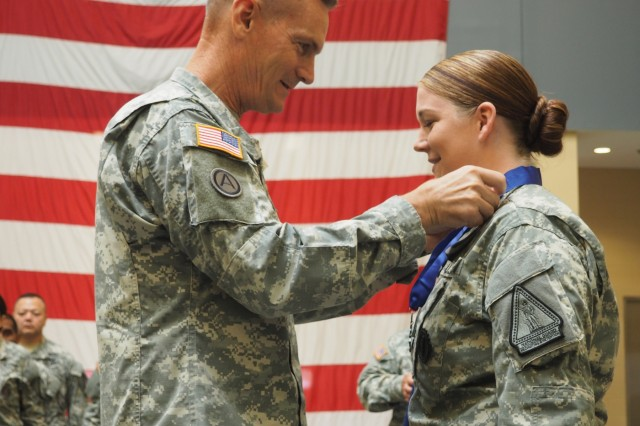 New York Army National Guard Major Gen. Patrick Murphy, adjutant general of New York, presents the New York State Medal for Valor, the state's highest military award, to Staff Sgt. Marlana Watson at the Armed Forces Reserve Center in Farmingdale, N.Y., Aug. 19, 2015.