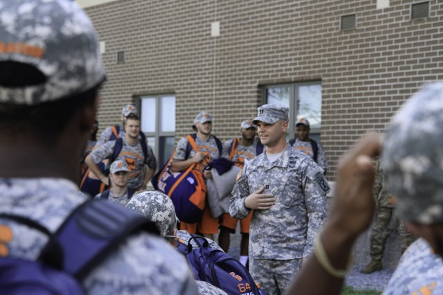 Capt. John Goodwill, Headquarters and Headquarters Company commander, 2nd Battalion, 87th Infantry Regiment, 2nd Brigade Combat Team, introduces himself to Syracuse Orange Football players as they arrive on Fort Drum Aug. 17. Players and Soldiers spent the next four days developing leadership skills through team building events that included, a confidence course, rappel tower, paintball and a pugil stick tournament.