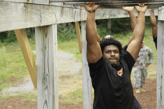 Chris Slayton, defensive tackle, Syracuse Orange football team, navigates the monkey bars on one of Fort Drum's obstacles at the confidence course Aug. 18. The confidence course emphasized teamwork for the players who encouraged and helped many of their teammates to do something they normally wouldn't do.