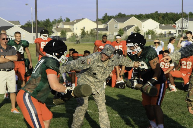Sgt. 1st Class Shane Hankey, center, operations non-commissioned officer, 2nd Brigade Combat Team, referees a pugil stick bout between Syracuse Orange Football players on Fort Drum Aug 18.