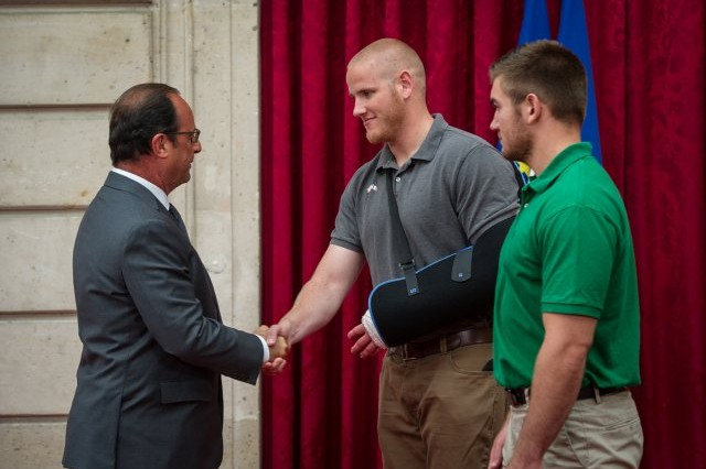 French President Francois Hollande congratulates Air Force Airman 1st Class Spencer Stone, left, and National Guard Spc. Aleksander Skarlatos, right, in Paris, Aug. 24, 2015, upon awarding them the Legion d'Honneur, France's highest honor, for subduing a gunman on a train.