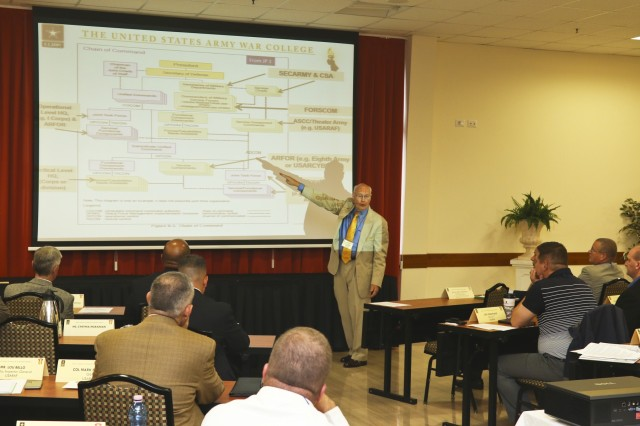 John Bonin, a professor at the Army War College, briefs the roles and responsibilities of an Army service component command to attendees of the U.S. Army Africa Senior Leader Strategy and Orientation Session in the Golden Lion conference center at Vicenza, Italy, Aug. 19, 2015.