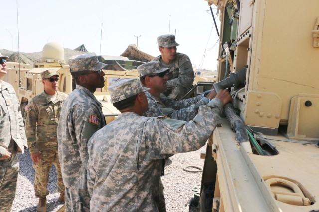 Soldiers gather around a system integrated onto an Army vehicle as they prepare for the Network Integration Evaluation 16.1/Army Warfighter Assessment.