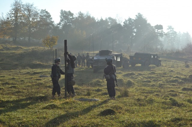 Soldiers  from the 428th & 309th Engineer Companies (Mobility Augmentation), stationed in Wausau, Wis., and Brainerd, Minn., emplace a row of pickets for a triple strand concertina wire obstacle during an operational forces training exercise at Hohenfels, Germany, Nov. 1 2014. (U.S. Army photo by Spc. Santiago Alameda/Released)