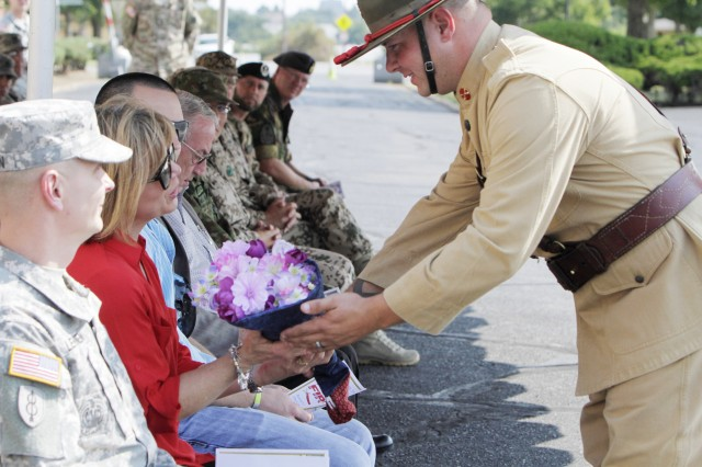 A Field Artillery Half-Section Soldier hands Elizabeth Lehtonen a bouquet of flowers during a retreat ceremony Aug. 21, 2015, outside McNair Hall. Her husband, Command Sgt. Maj. Robert Lehtonen is taking over as the field artillery branch and Field Artillery School command sergeant major.