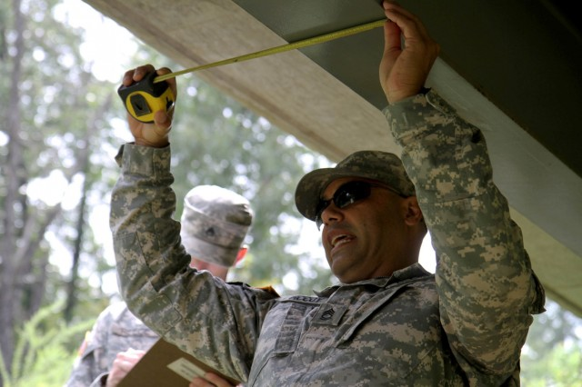 Sgt. 1st Class Gregory McCoy, of the 801st Engineer Company, out of Mare Island, Calif., and a student of the Horizontal Construction Engineers Senior Leader Course takes measurements to calculate the rapid classification of a fixed bridge at the Fort Leonard Wood, Mo. multi-purpose bridge site.