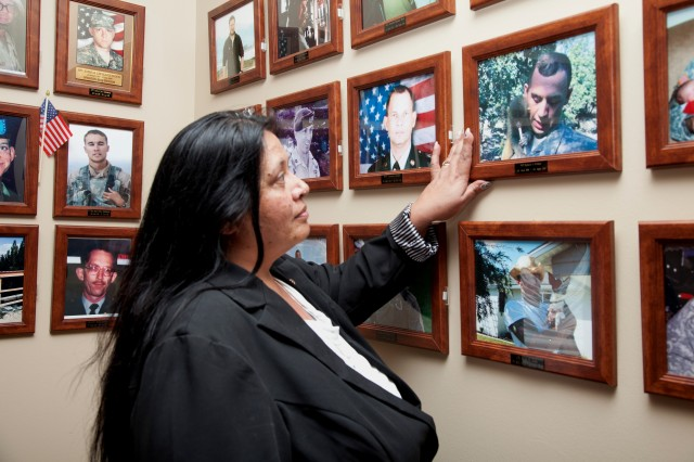Gold Star mother Brenda Cox views a photo of her son Pfc. Richard Allen DeWater at the Survivor Outreach Services Remembrance Hall in Fort Hood, Texas. Cox credits Survivor Outreach Services staff members for helping her cope with her son's loss.