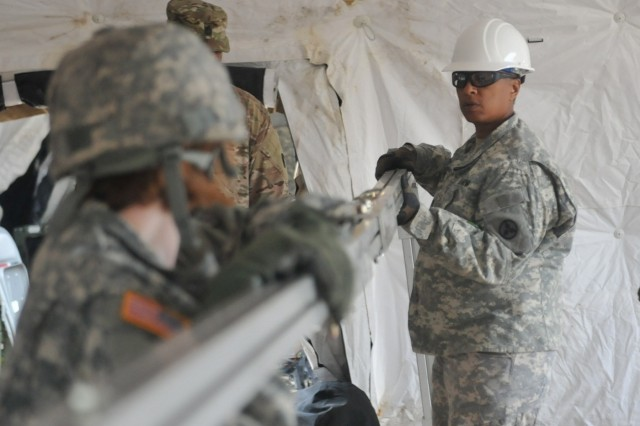 Spc. Kristin Day (left), a human resources specialist, and Capt. Wanda Henderson (right), a medical plans and operations officer, both with the 3rd Expeditionary Sustainment Command, help move a support beam into place as part of the Early Entry Command Post setup, Aug. 17, at Rhine Ordnance Barracks in Kaiserslautern, Germany. The 3rd ESC was deployed to support the XVIII Airborne Corps during operation Swift Response. (U.S. Army photo by Staff Sgt. Justin Silvers)
