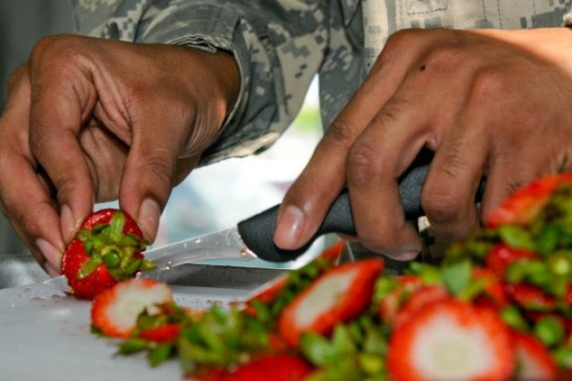 Pvt. Daniel Marte Pena, a food service specialist with the 302nd Maneuver Enhancement Brigade a reserve unit based in Mass., uses precision while cutting strawberries for a fruit salad while participating in the Task Force 76's Digital Command Post Exercise.