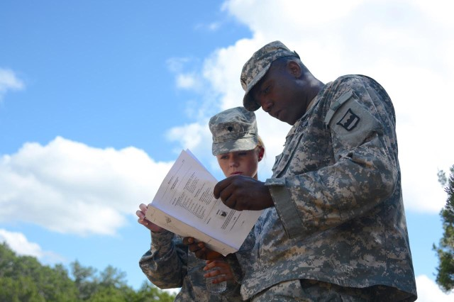 Spc. Felicia Boling (left), from the 3/379th Logistics Support Battalion, with Sgt. Ronald Manigat, of the 4/321 LSB, study the technical manual prior to being questioned on how to properly change a tire during the 2015 80th Training Command Logistics Training Exercise hosted by the 800th Logistics Support Brigade and conducted by the 3/379th LSB.  The three day event, which started on Sept. 1,  assesses the competence level of truck drivers and wheeled vehicle mechanics within the brigade.