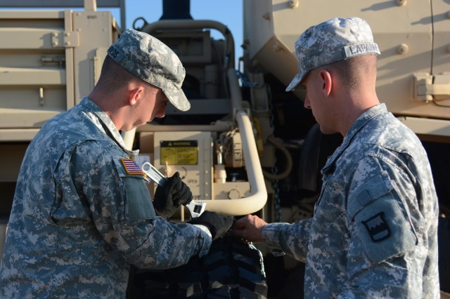 Spc. Coady Reynolds (left) and Spc. David Lapanne (right), a two-person team representing 3/319 Logistics Support Battalion, compete in the tire changing event of the 2015 80th Training Command Logistics Training Exercise hosted by the 800th Logistics Support Brigade and conducted by the 3/379th LSB.  The three day event, which started on Sept. 1, assesses the competence level of truck drivers and wheeled vehicle mechanics within the brigade.