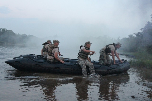 A combat engineer team dismounts and prepares to carry a zodiac boat from the water as part of a non standard Army Phisical Fitness Test during Sapper Stakes 2015 at Fort Chaffee, Ark., Aug. 30. Sapper Stakes is a nationwide competition for Army Reserve and National Guard Soldiers, allowing Sapper teams to compete to develop teamwork and enhance leadership. (U.S Army Photo by Sgt. Devin M. Wood)