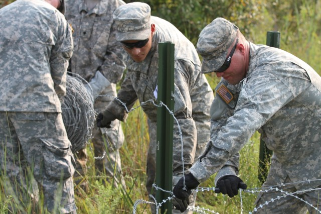A combat engineer team uses concertina wire and steel pickets to construct and 11-row fence during Sapper Stakes 2015 at Fort Chaffee, Ark., Sep. 1. Sapper Stakes is a nationwide competition allowing Army Reserve and National Guard Sapper teams to compete to develop teamwork and enhance leadership. (U.S Army Photo by Sgt. Devin M. Wood)