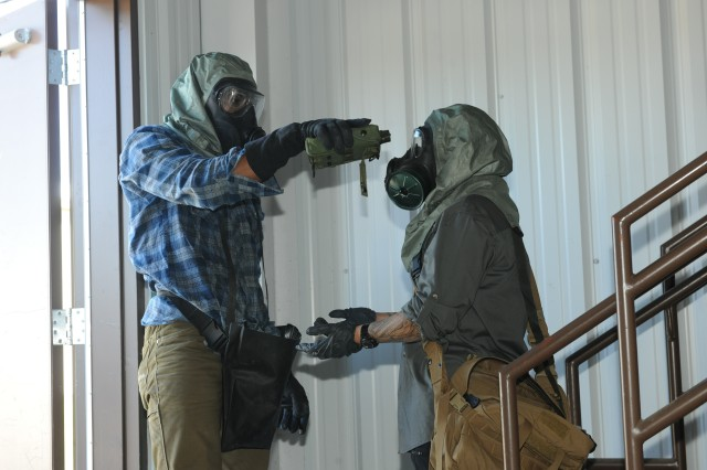 From left, Pvt. Daniel Boiten, chemical specialist from Fort Carson, simulates the decontamination process of Sgt. Lizy Lozano, also a chemical specialist, as she exits a building at the Incidence Response Training Department during a unit certification training operation Aug. 26 at Fort Leonard Wood.