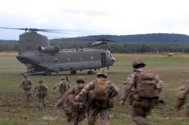 British paratroopers run toward a British helicopter for extraction from Range 118 on the Grafenwoehr Training Area (Germany) during a live fire event as part of exercise Swift Response 15, Sept. 2, 2015.