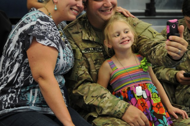 Staff Sgt. Douglas Dolliver, Headquarters and Headquarters Battalion, III Corps, takes a quick Family snapshot with his wife, Melissa, and daughter, Riley, inside the Abrams Physical Fitness Center at Fort Hood, Texas, Aug. 29, prior to loading buses bound for Robert Gray Army Airfield and a deployment in support of Operation Inherent Resolve. (U.S. Army photo by Nick Conner, Fort Hood Public Affairs)