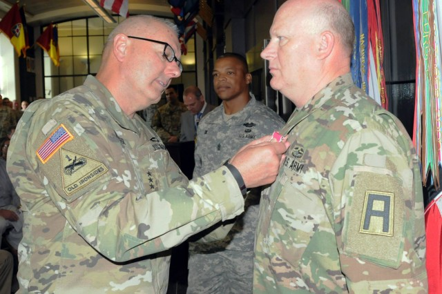 """Lt. Gen. Michael S. Tucker, First Army commanding general, pins the Legion of Merit on Maj. Gen. James K. """"Red"""" Brown during a hail and farewell ceremony for the deputy commanding general-operations on September 3 in First Army headquarters."""