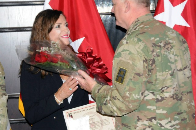 """Maj. Gen. James K. """"Red"""" Brown presents flowers to his wife, Jane, during a hail and farewell ceremony for the First Army deputy commanding general-operations on September 3 in First Army headquarters."""