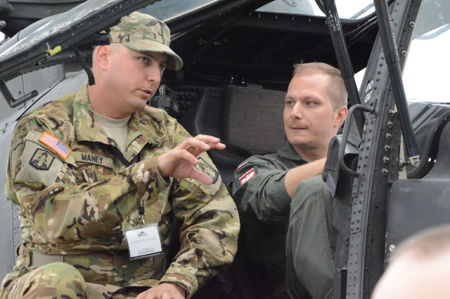 Chief Warrant Officer Two Andrew Maney, assigned to 2nd Battalion, 159th Attack Reconnaissance Aviation Regiment, 12th Combat Aviation Brigade, explains the operational capablities of the AH-64 Apache to Polish Lieutenant Grezegorz Banaszek of the 7th Aviation Squadron of the 25th Air Calvary Brigade. (U.S. Army photo by Capt. Jaymon Bell /released)