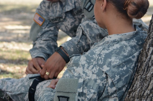 CAMP BULLIS, Texas - Sgt. Christopher Smith, a competitor from the 3/379th Logistics Support Battalion, applies a combat application tourniquet on Spc. Kristina Singleton, a competitor from the 3/399th LSB, as a part of the warrior task lanes held during day three of the 2015 80th Training Command (TASS) 'Truck Rodeo' competition. The three-day competition hosted by the 800th Logistic Support Brigade, which started on Sept. 1, assesses the competence level of truck drivers and wheeled vehicle mechanics within the 80th Training Command (TASS).