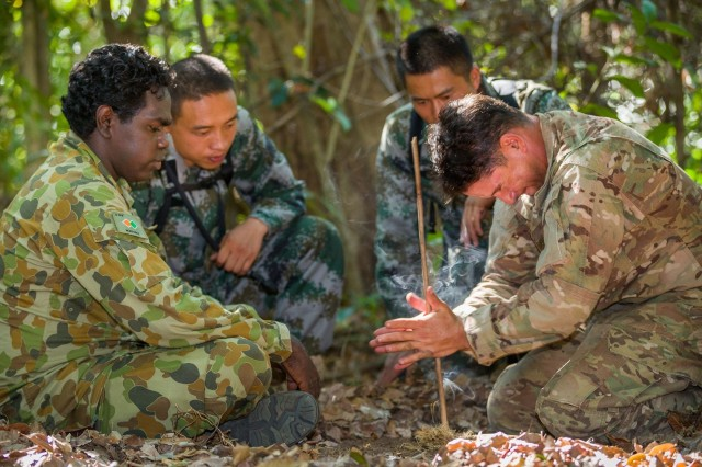 Australian Army soldier Lance Cpl. Vinnie Rami (left) guides U.S. Army Soldier Sgt. 1st Class Adam Marques (right) through creating fire using the traditional 'drill' method during Exercise Kowari 2015 in the Daly River region, Northern Territory, Australia, Sept. 1, 2015.
