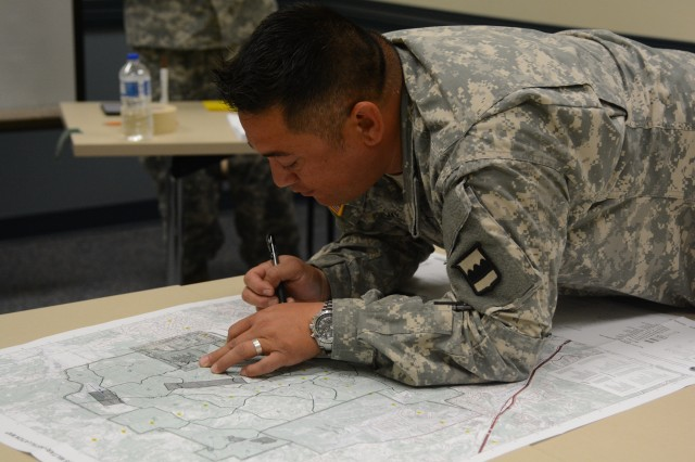 CAMP BULLIS, Texas -- 1st place winner in the driver category, Staff Sgt. Joseph Cook, a competitor 3/399th Logistics Support Battalion plots points on a map during the land navigation portion of the warrior task lanes on day three of the 2015 80th Training Command Logistics Training Exercise hosted by the 800th Logistics Support Brigade.
