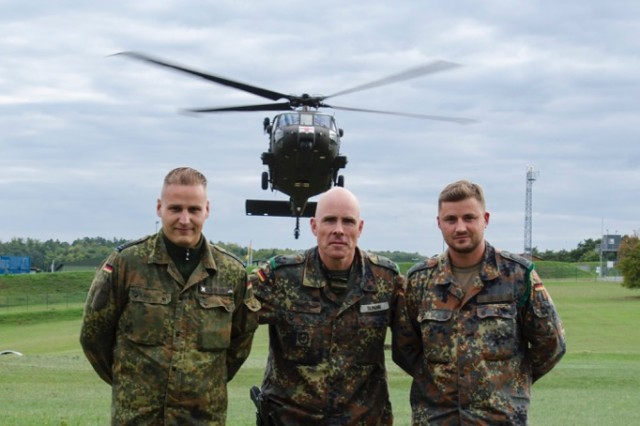 Lt. Col. Jan-Friedrich Tilman (center), commanding officer of 401 Armored Infantry Battalion, stands with Master Sgt. Ronny Beyer (left) and Master Sgt. Andreas Schramm (right), as a HH-60 Medevac Black Hawk from 4th Battalion, 3rd Aviation Regiment hovers in the background. Beyer and Schramm received the prestigous German Bundeswehr retirement contract from Lt. Col Tilman.A total of 208 German Bundeswehr Soldiers, participated in aircraft familiarization and medical evacuation (MEDEVAC) training supported by 4-3 Assault Helicopter Battalion, Sept. 8-9, at the Hammelburg Training Area, Germany.